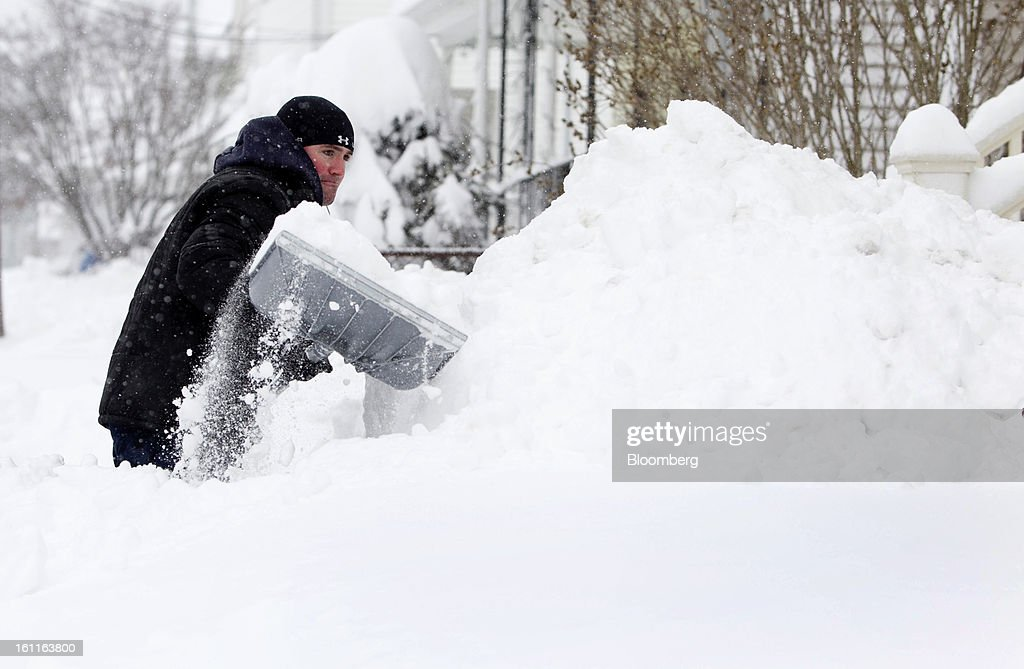 Resident David Haughton shovels the sidewalk outside his home after Winter Storm Nemo in Somerville, Massachusetts, U.S., on Saturday, Feb. 9, 2013. More than two feet of snow fell on parts of the U.S. Northeast as high winds left hundreds of thousands of people in the region without power, closed highways and forced the cancellation of 4,700 flights. Photographer: Kelvin Ma/Bloomberg via Getty Images