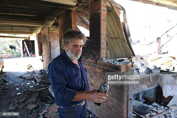 Resident David Miller carries a wine bottle that melted in the intensity of the heat when his home near Kersbrook was destroyed by a bushfire in the...