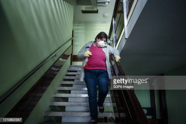 Resident disinfects a staircase way while wearing a protective mask as a preventive measure during the Coronavirus lockdown crisis. Slovenia has...