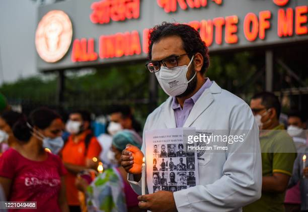 Resident doctors of All India Institute of Medical Science light candles as a tribute to the martyrs of Galwan valley faceoff outside AIIMS hospital...