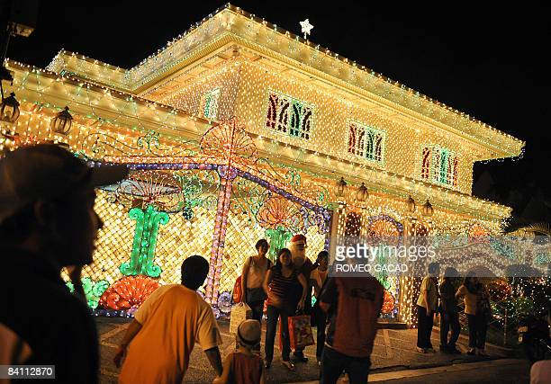 Resident dressed as Santa Claus entertains visitors viewing the house of Filipino businessman Domingo Dalisay wrapped in Christmas lights, in...