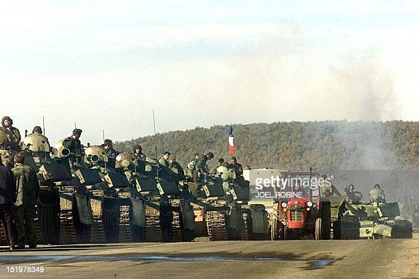 A resident drives his tractor 29 October past a convoy of Serb tanks rolling near Pec on the way back to their barracks in the Kosovo's capital The...