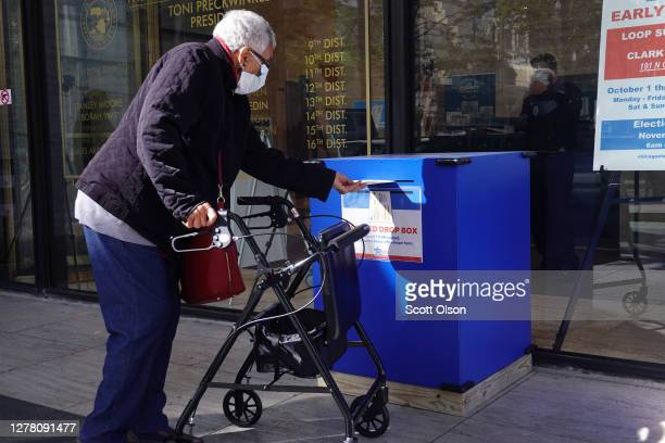 Resident drops off a vote-by-mail ballot in a secure drop box on October 02, 2020 in Chicago, Illinois. The city opened its first early voting site...