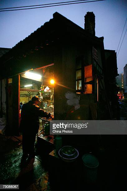 Resident fetches hot water at a Laohuzao teahouse at an alleyway January 23, 2007 in Shanghai, China. Laohuzao is a traditional store which sells hot...