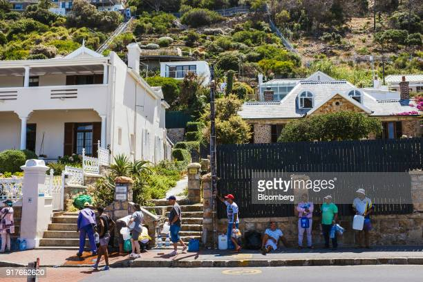 Resident fill plastic water bottles and containers from a natural water spring in St James Cape Town South Africa on Thursday Feb 8 2018 Confronted...