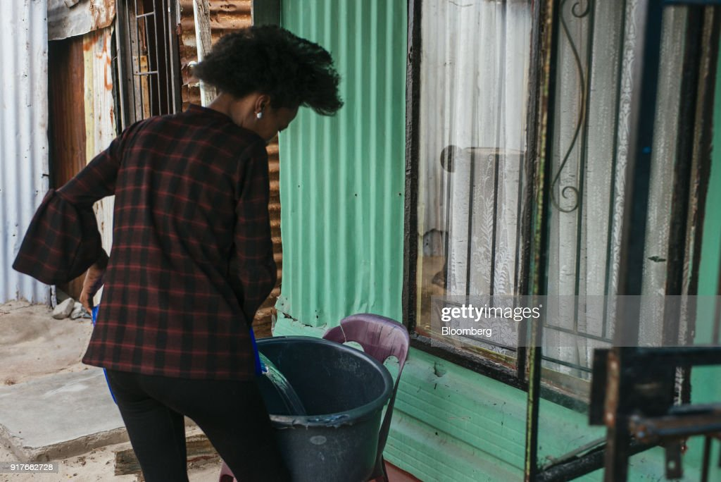 A resident fills a plastic container with water collected from a communal tap, to be used for hand washing clothing in the Khayelitsha township, Cape Town, South Africa, on Friday, Feb. 9, 2018. Confronted by the worst drought on record after years of disastrously low rainfall, city authorities say they may have to turn off the water entirely on May 11, the famous 'Day Zero,' if reservoir levels keep falling and consumption doesn't slow enough. Photographer: Waldo Swiegers/Bloomberg via Getty Images