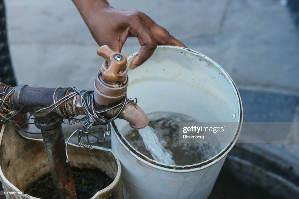 A resident fills a plastic container with water from a communal tap in the Khayelitsha township, Cape Town, South Africa, on Friday, Feb. 9, 2018. Confronted by the worst drought on record after years of disastrously low rainfall, city authorities say they may have to turn off the water entirely on May 11, the famous 'Day Zero,' if reservoir levels keep falling and consumption doesn't slow enough. Photographer: Waldo Swiegers/Bloomberg via Getty Images