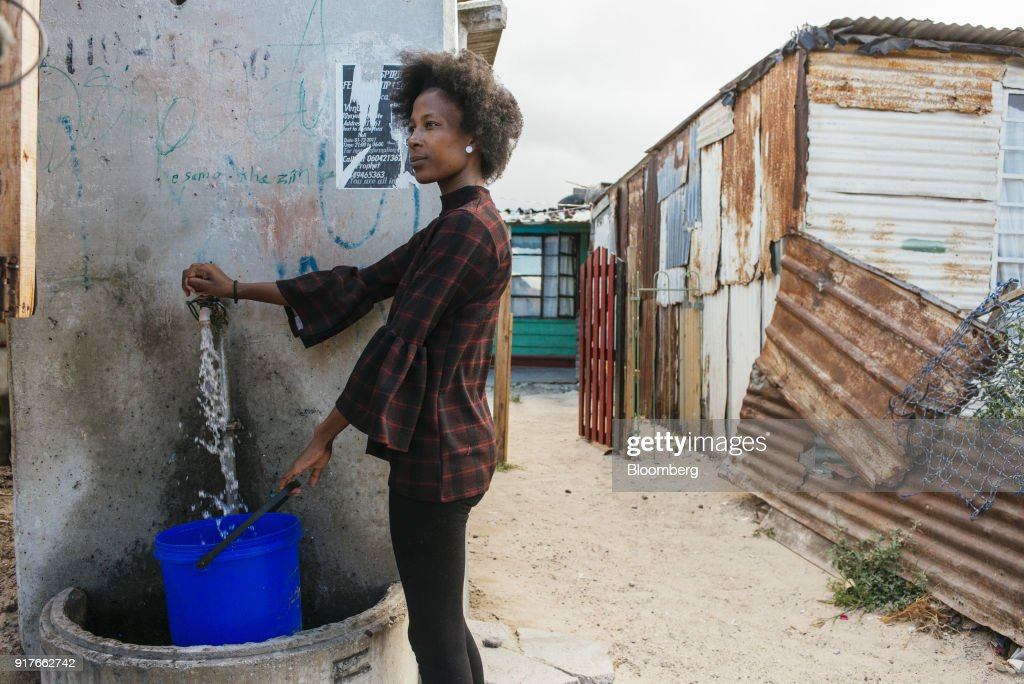 A resident fills a plastic container with water from the communal tap in the Khayelitsha township, Cape Town, South Africa, on Friday, Feb. 9, 2018. Confronted by the worst drought on record after years of disastrously low rainfall, city authorities say they may have to turn off the water entirely on May 11, the famous 'Day Zero,' if reservoir levels keep falling and consumption doesn't slow enough. Photographer: Waldo Swiegers/Bloomberg via Getty Images