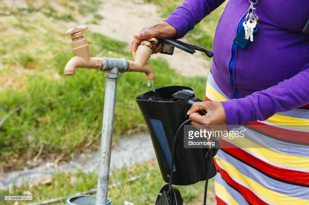 A resident fills a plastic kettle with water from a communal tap in the Imizamo Yethu township outside Cape Town South Africa on Monday Nov 13 2017...
