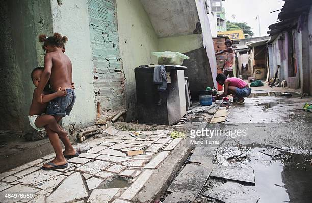A resident fills water from the one running water pipe that serves dozens of residents in a section of the Complexo da Mare 'favela' complex one of...