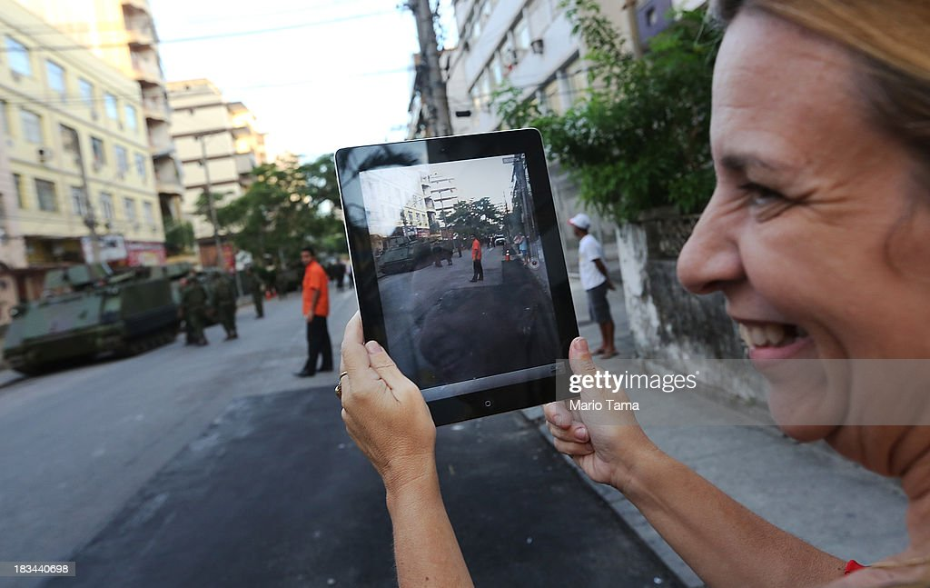 A resident films on her iPad as military forces wait to start a 'pacification' operation in the nearby favela complex of Lins de Vasconcelos, in the North Zone, on October 6, 2013 in Rio de Janeiro, Brazil. The favela complex, or shanty town, was previously controlled by drug traffickers and will now be occupied by the city's 35th UPP or 'Police Pacification Unit'. The favela pacifications are occurring amid Rio de Janeiro's efforts to improve security ahead of the 2014 FIFA World Cup and 2016 Olympic Games.