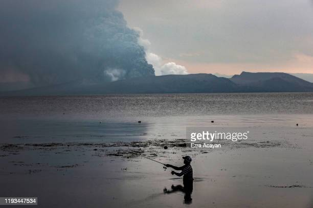 A resident fishes at a lake as Taal Volcano erupts on January 13 2020 in Balete Batangas province Philippines The Philippine Institute of Volcanology...