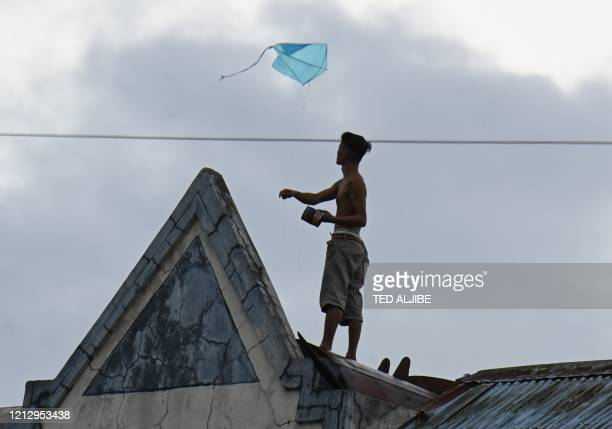 A resident flies his kite with rain clouds above atop his house inside a tenement building in Manila on May 14 as Typhoon Vongfong approaches A...