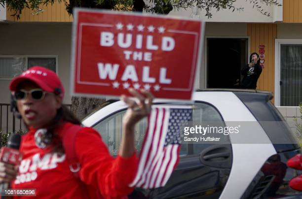 A resident flips his finger at a Pro Donald Trump supporter as she marches through a neighborhood near a Border Patrol station on January 12 2019 in...
