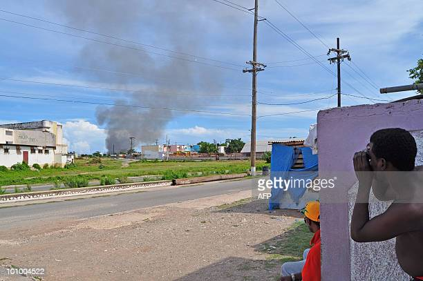 A resident from Trench Town uses binoculars to look at smoke billowing in the Tivoli neighborhood of Kingston Jamaica May 24 2010 Gun battles raging...
