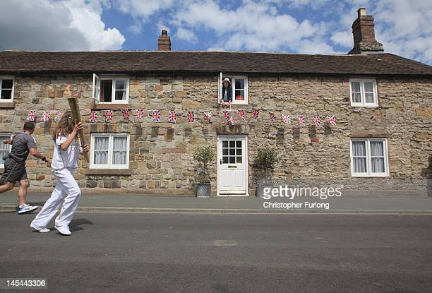 Resident Gabrielle Drake looks out of the window of Hollybush Cottage as the Olympic Torch passes through Much Wenlock the birthplace and former home...
