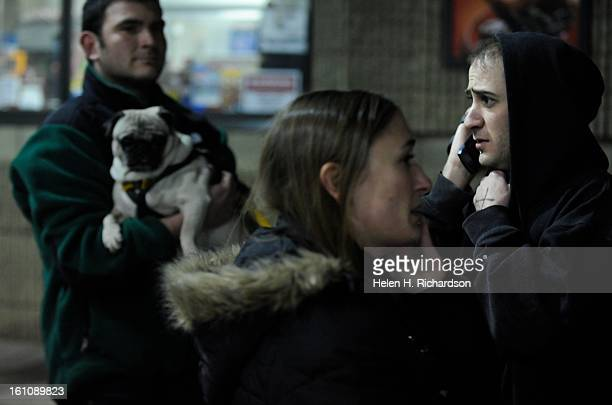 Resident Garrett Gwin right talks on the phone after he was displaced by the fire Friend Jeffrey Weimar holds Gwin's dog Skyler at left and his...