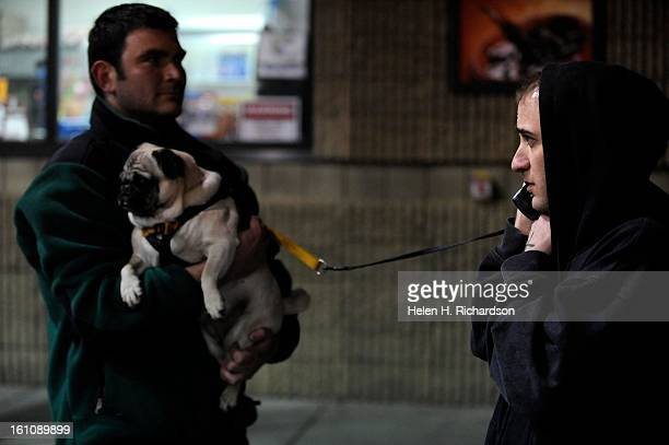 Resident Garrett Gwin talks on the phone after he was displaced by the fire Friend Jeffrey Weimar holds Gwin's dog Skyler Gwin and his girlfriend...