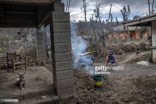 A resident grills fish along a road covered in volcanic ash from Taal Volcano's eruption on January 20 2020 in the village of Buso Buso Laurel...