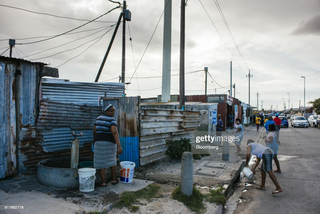 A resident hand washes clothing in a plastic container at a communal tap in the Khayelitsha township, Cape Town, South Africa, on Friday, Feb. 9, 2018. Confronted by the worst drought on record after years of disastrously low rainfall, city authorities say they may have to turn off the water entirely on May 11, the famous 'Day Zero,' if reservoir levels keep falling and consumption doesn't slow enough. Photographer: Waldo Swiegers/Bloomberg via Getty Images