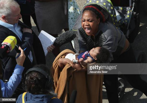 A resident holding her baby shouts out during a spontaneous protest at the Bavarian Transit Centre Manching/Ingolstadt for asylumseekers on May 15...