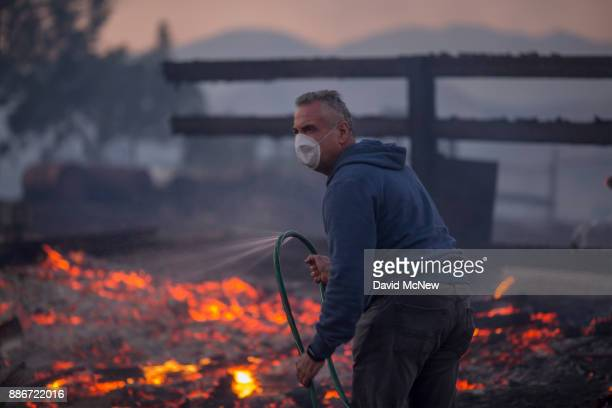 A resident holds a leaking hose on his burning property during the Creek Fire on December 5 2017 in Sunland California Strong Santa Ana winds are...