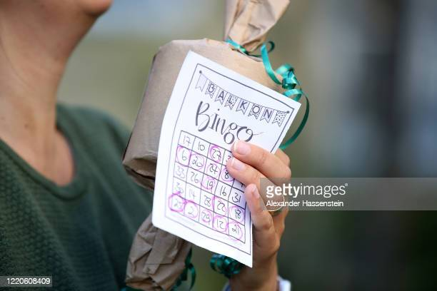 Resident holds the winning gift, a roll of toilet after playing bingo from their balconies with performing artist Max Auerbach during the novel...