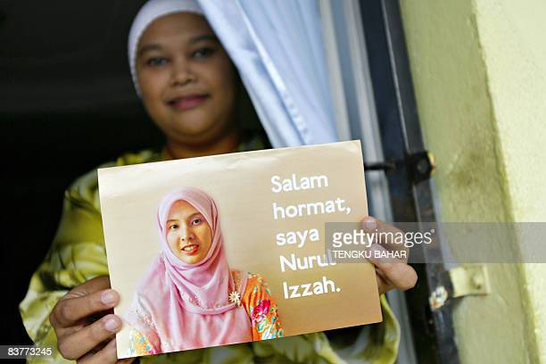 A resident holds up a campaign leaflet carrying the portrait of opposition People's Justice Party candidate Nurul Izzah Anwar daughter of former...