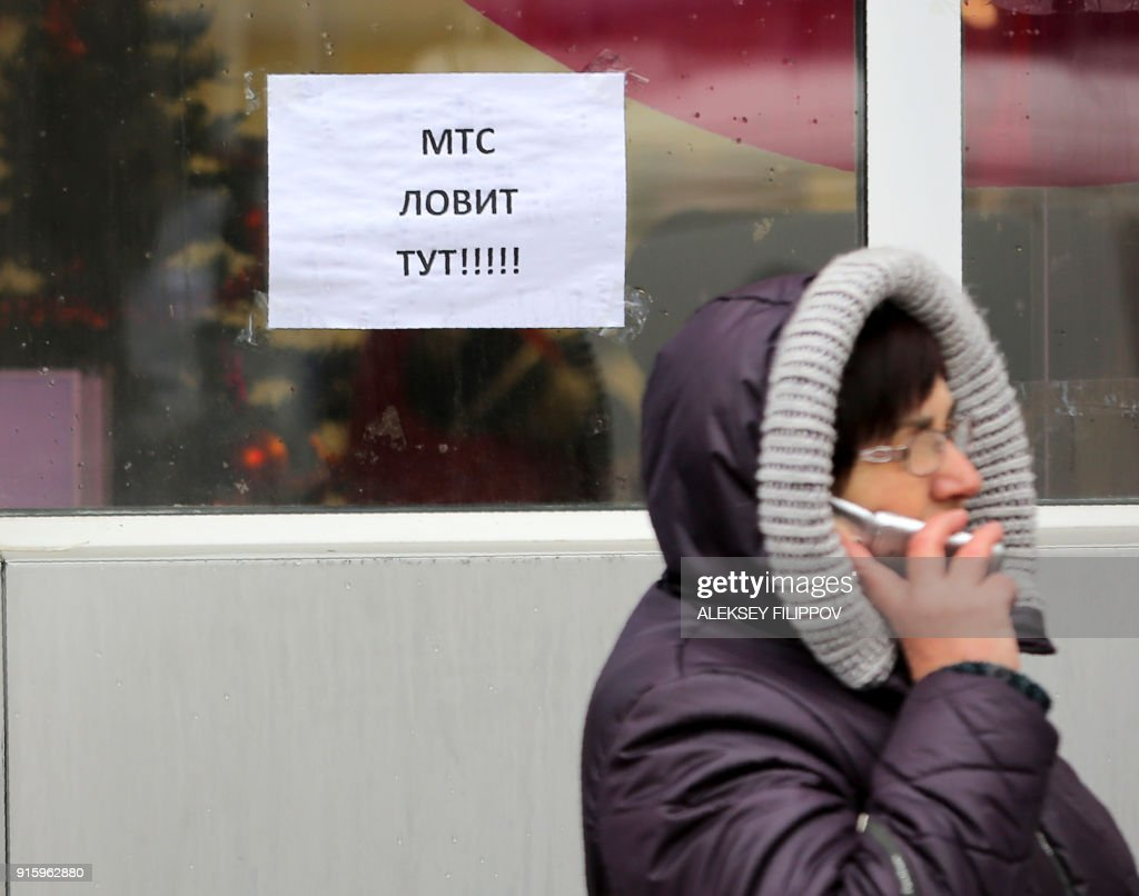 A resident in the hope of catching a signal from cell towers makes a call by a leaflet reading 'MTS is available here' in one of the few places available for mobile connection provided by Vodafone Ukraine (former MTS) in Donetsk on February 2, 2018. Every day dozens of people in the Ukrainian rebel stronghold of Donetsk gather on a windswept railroad overpass not far from the frontline despite the risk of coming under fire. They come to the bridge at a half-abandoned railway station on the outskirts of the city in the hope of catching a signal from cell towers on the other side of the frontline to be able to call their family and friends in government-controlled territories. PHOTO / Aleksey FILIPPOV