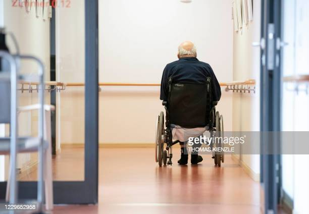 Resident in the wheelchair makes his way on a floor in the retirement home St. Barbara of German welfare organisation Caritas in Stuttgart, southern...
