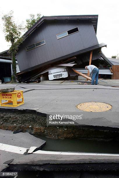 A resident inspects property damage October 24 2004 in Ojiya Niigata Prefecture Japan A series of powerful earthquakes damaged northern Japan...