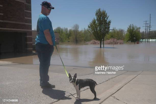 Resident inspects the floodwaters flowing from the Tittabawassee River into the lower part of downtown on May 20, 2020 in Midland, Michigan....