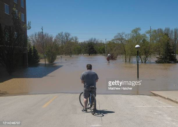 A resident inspects the floodwaters flowing from the Tittabawassee River into the lower part of downtown on May 20 2020 in Midland Michigan Thousands...