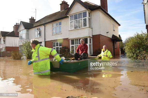 A resident is rescued from a home in a boat by the emergency services amid flooding in Hereford western England on February 17 in the aftermath of...