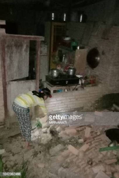 A resident is seen beside the collapsed brick wall of her house at Tobadak village in Central Mamuju western Sulawesi province on September 28 after...