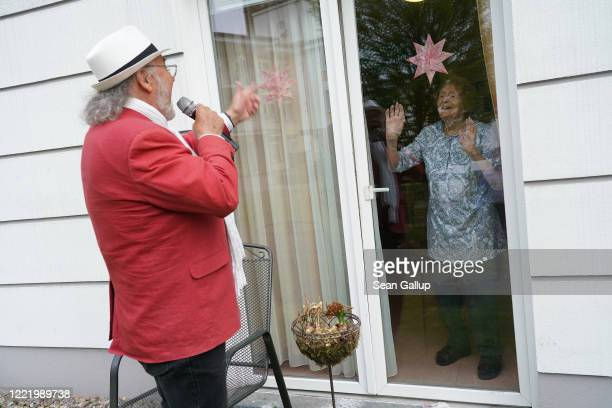 Resident Johanna Pfeiffer looks on from her room as singer Alf Weiss performs live at the Hermann Radtke Haus nursing home during the novel...