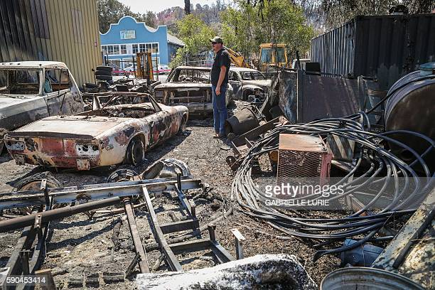TOPSHOT Resident John Weidner surveys the damage to his friends' cars in the Clayton Fire at the Clearlake machine shop in Lower Lake California...