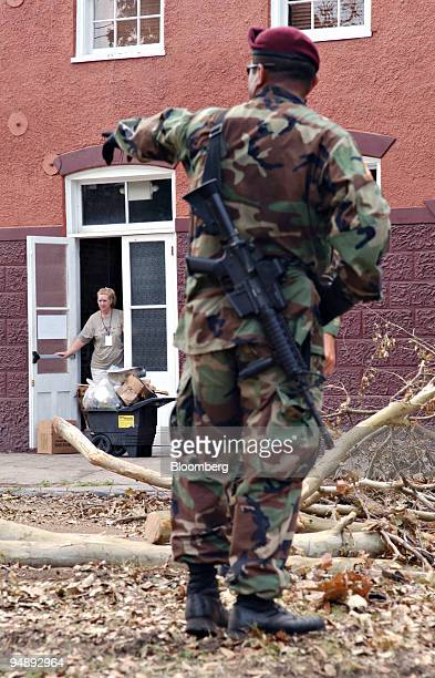 Resident Karen Lott stands in a doorway as a a member of the 307 Engineers attached to the 82 Airborne out of Fort Bragg Texas directs cleanup in the...