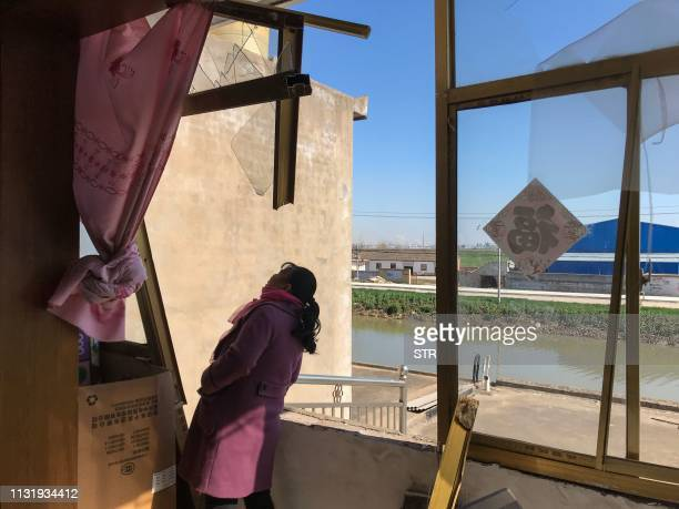 A resident looks at a broken windows after an explosion in Yancheng in China's eastern Jiangsu province early on March 22 2019 The death toll from a...