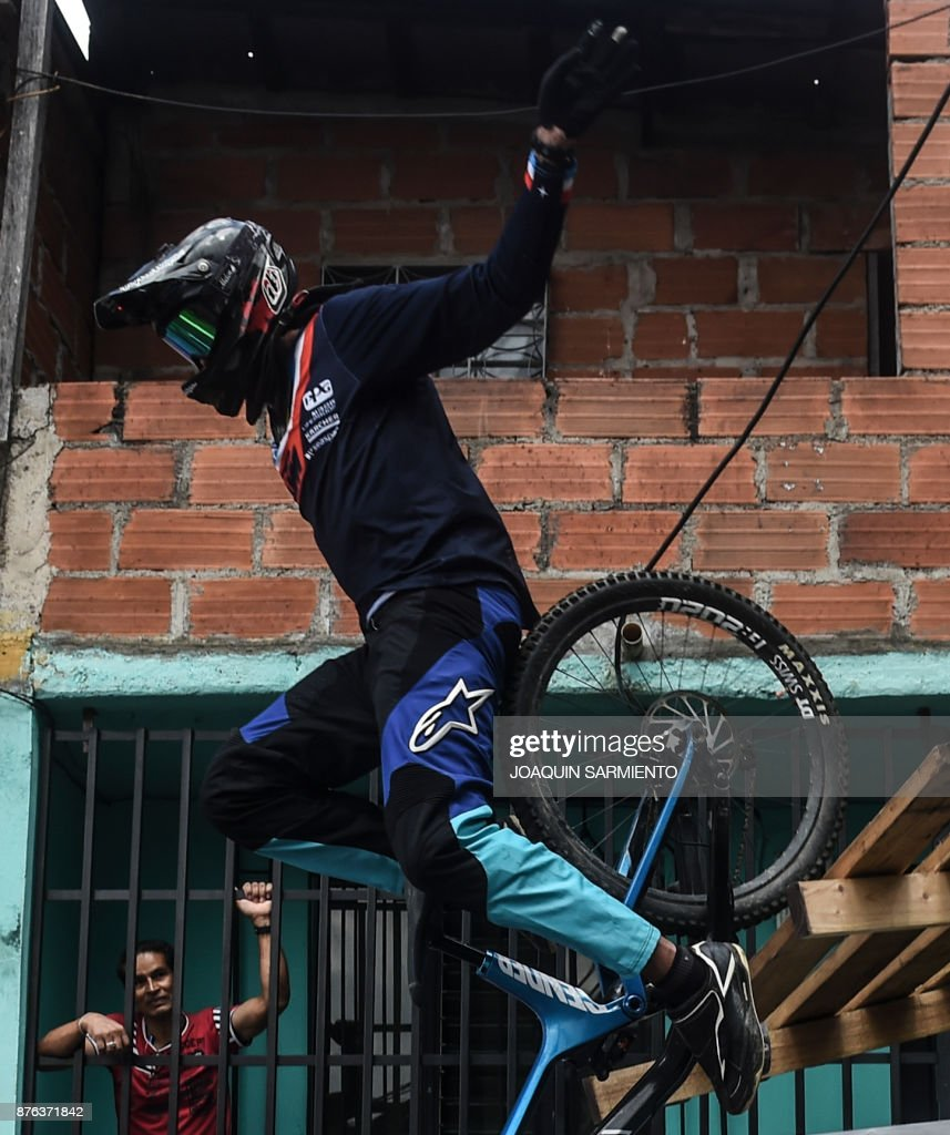 A resident looks at a downhill rider during the Urban Bike Inder Medellin race final at the Comuna 1 shantytown in Medellin, Antioquia department, Colombia on November 19, 2017. /