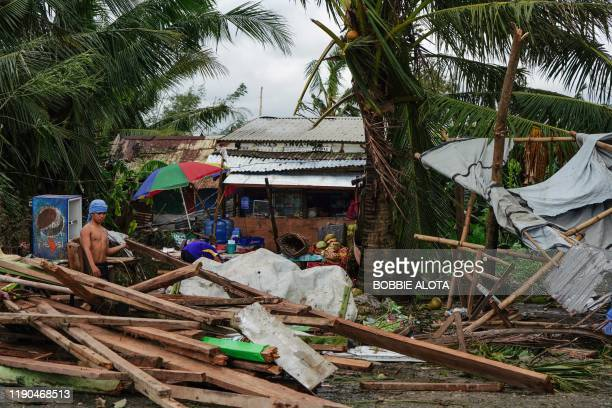 TOPSHOT A resident looks at a house damaged at the height of Typhoon Phanfone in Tacloban Leyte province in the central Philippines on December 25...