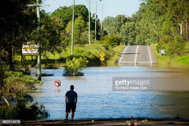 TOPSHOT A resident looks at a road submerged under floodwaters caused by Cyclone Debbie in North MacLean Brisbane on April 1 2017 Flooded rivers were...