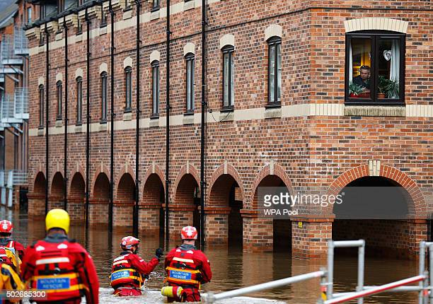 A resident looks down at members of the emergency services in flood water in York city centre after the river Ouse burst its banks on December 28...
