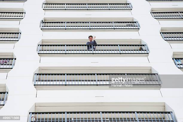 A resident looks down from his apartment at the Auckland Harbour Oaks Apartments on December 5 2015 in Auckland New Zealand Police are hunting for a...