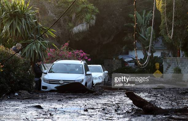 A resident looks into her car that sits in mud and debris from a mudslide on January 11 2018 in Montecito California 17 people have died and hundreds...