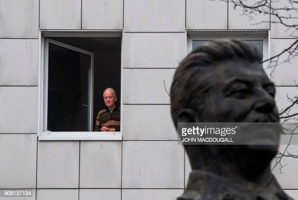 Resident looks on as a 4,8-metre-high statue of former Soviet dictator Joseph Stalin is lifted by a crane on Berlin's Karl-Marx Allee on January 23,...