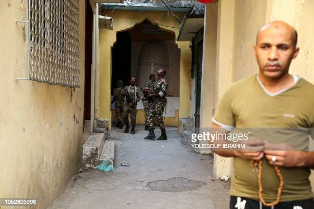 A resident looks on as Comoros Armed forces members search and patrol the 'Medina' for weapons and armed men at Mutsamudu on October 20 2018 on the...