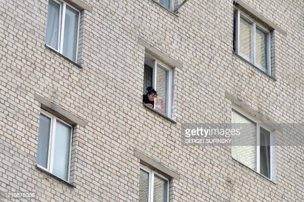 A resident looks out from a window of a hostel closed for hard quarantine due to an outbreak of the COVID19 coronavirus in the small Ukrainian town...