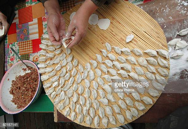 A resident makes Chinese dumplings on Chinese New Year's Eve February 8 2005 in Fu County Shaanxi Province China Making dumplings which symbolize the...