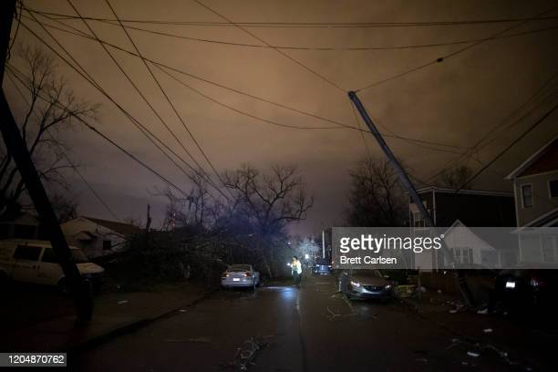 A resident makes her way down Underwood St amidst downed trees and heavy debris on March 3 2020 in Nashville Tennessee A tornado passed through...